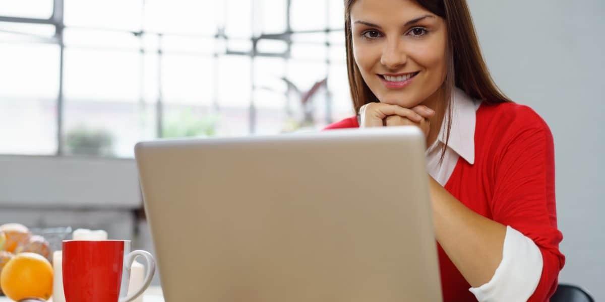 kobieta w trakcie spotkania online, siedząca przy stole z laptopem i kawą