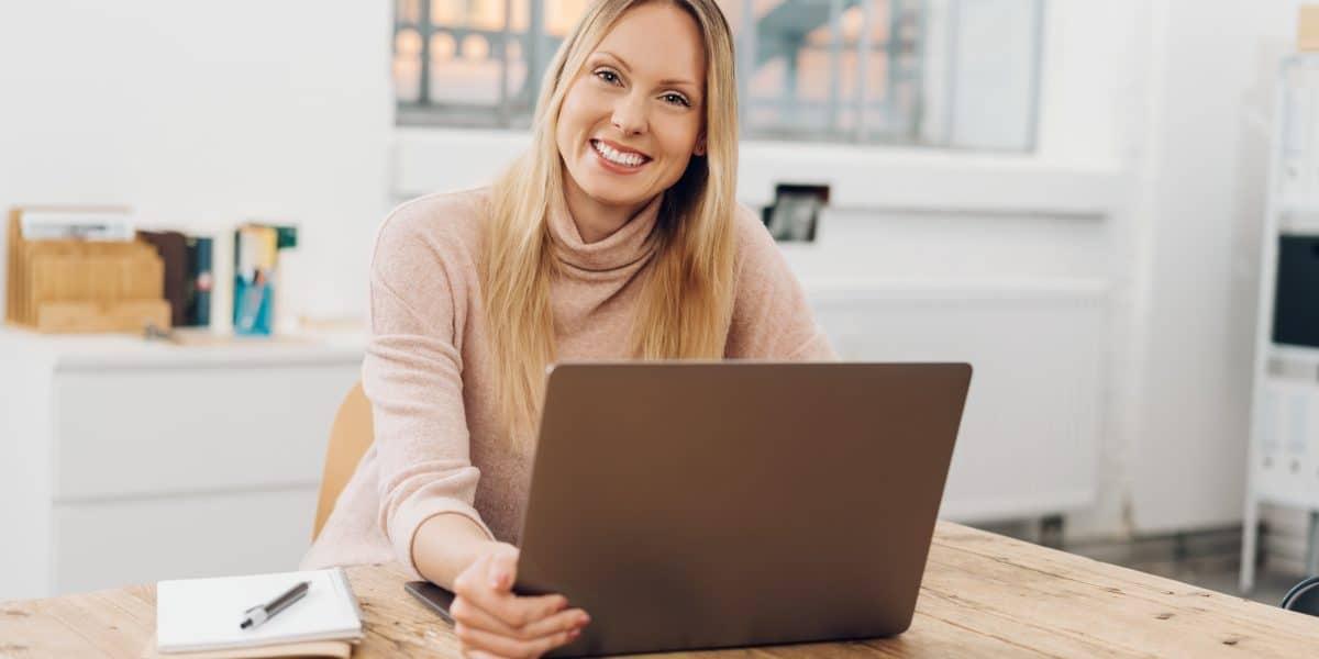 Uśmiechająca się młoda kobieta z laptopem