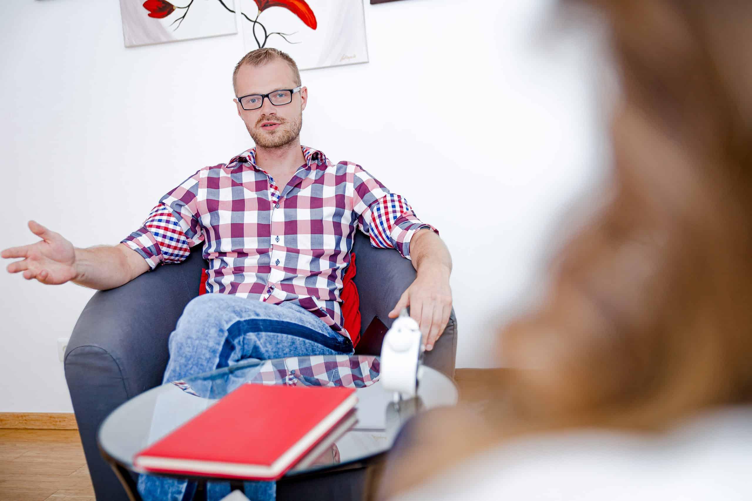 mężczyzna rozmawia z kobietą w gabinecie psychologicznym